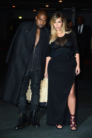 Kim Kardashian showed off her ample cleavage in a sheer-panel black evening dress during the Givenchy fashion show.