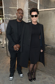 Kris Jenner kept it understated in a wool coat layered over an LBD at the Givenchy Menswear fashion show.