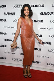 A nude Ferragamo hard-case clutch with gold hardware completed Freida Pinto's ensemble.