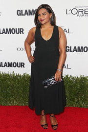 For a touch of print to her plain black outfit, Mindy Kaling accessorized with a floral clutch by Jimmy Choo.