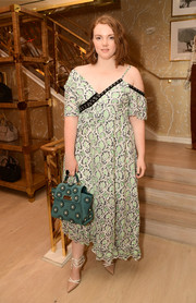 Shannon Purser completed her ensemble with a pearl-embellished teal suede tote by Zac by Zac Posen.