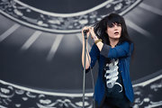 Alison Mosshart rocks on stage with her hair styled in a long straight cut with front bangs.