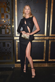 Elsa Hosk flashed plenty of flesh at the Gold Obsession Party in a black Versace one-sleeve gown featuring a pair of bodice cutouts and a high side slit.