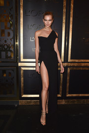Karlie Kloss looked totally alluring at the Gold Obsession Party in a black Brandon Maxwell one-shoulder gown that was slit all the way up to the hip.