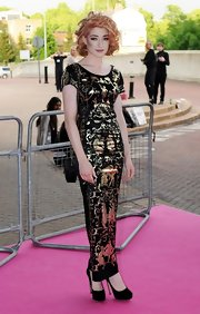 Nicola kept all eyes on a dramatic floor length sheath by pairing the gilded dress with classic black suede platforms.
