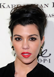 Kourtney Kardashian wore a glossy finish lipstick in a vibrant red shade at the Las Vegas opening of Kardashian Khaos.
