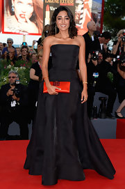 Golshifteh's strapless black gown not only flattered her figure but let her red clutch pop.