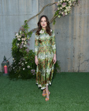 Dakota Johnson added a dazzling pop of color with a pair of bright-orange crisscross-strap heels, also by Gucci.