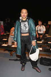 Paloma Elsesser accessorized with an asymmetrical white leather purse.