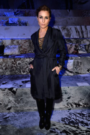 Noomi Rapace covered up with a dark blue H&M duster coat for the label's fashion show.
