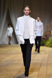 Amber Valletta looked smart in a loose white blazer layered over a ruffle-neck blouse while walking the H&M runway.
