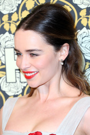 Emilia Clarke showed off her pearly whites with a swipe of red lipstick to match the floral designs on her dress.