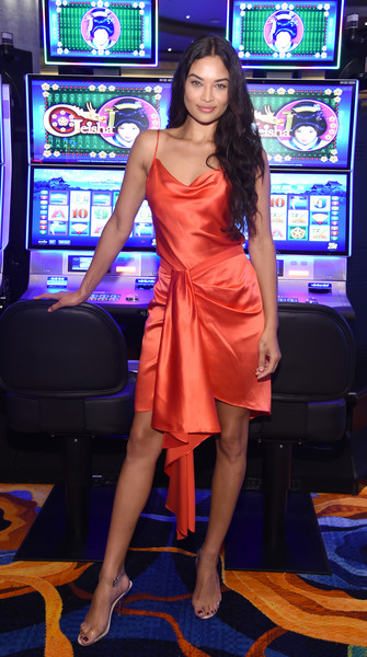 Shanina Shaik hit the HQ2 opening night wearing a draped red-orange slip dress.