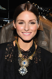 Olivia Palermo loves to accessorize her look. She paired lace blouse with a gold chain necklace full of gemstone adornments.