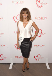 Halle Berry chose a black leather pencil skirt to team with her blouse.