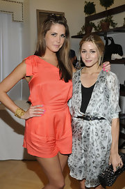 Erin wears a gold cuff bracelet with her salmon jumper for a picture with Olivia Palermo.