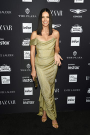 Adriana Lima got glam in a gold off-one-shoulder gown by Vivienne Westwood Couture for the 2018 Harper's Bazaar Icons event.