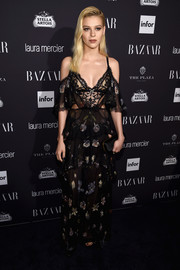 Nicola Peltz turned up the heat in an Alexander McQueen semi-sheer, lace-bodice floral gown at the Harper's Bazaar Icons event.