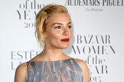 Sienna Miller contrasted her soft-hued dress with a bold red lip.