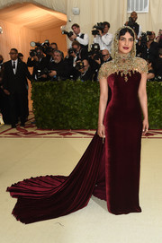 Priyanka Chopra looked opulent in a burgundy velvet gown by Ralph Lauren topped off with a glittering headpiece and collar.
