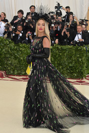 Rita Ora arrived in grand style at the 2018 Met Gala in a sequined Prada gown with an embellished tulle overlay and a seemingly endless train.