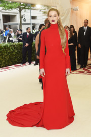 Amber Heard looked dazzling in a red Carolina Herrera turtleneck gown with a fishtail hem at the 2018 Met Gala.