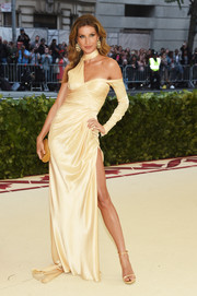 Gisele Bundchen struck a sexy pose wearing an asymmetrical yellow silk gown by Versace at the 2018 Met Gala.