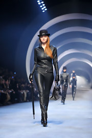 Supermodel Lily Cole struts the Hermes' Fall 2010 runway in a black leather catsuit and bowler hat.