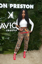 Remy Ma teamed her sexy top with a pair of printed pants by Heron Preston.