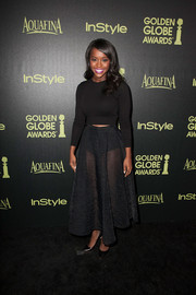 Aja Naomi King flashed a bit of abs in a cropped black Tracy Reese sweater during the Golden Globe Award season celebration.