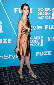 Emmy Rossum paired her sultry mocha satin dress with a bronze tube clutch.
