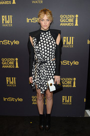 Riley Keough went the unconventional route in a black-and-white Louis Vuitton polka-dot dress with waist and sleeve cutouts during the HFPA and InStyle Golden Globe Award season celebration.