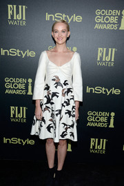 Jess Weixler wore a long-sleeved white dress with a bow on the top and bird motifs printed on the bottom of the gown