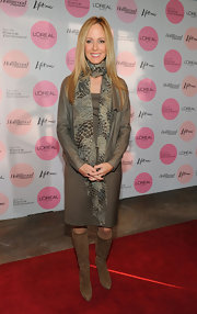 Dana wears a sheer snake skin scarf with her neutral toned ensemble.