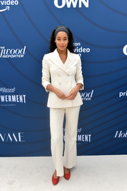 Laura Harrier gave her white look a pop of color with a pair of red pumps.