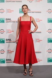 Rosamund Pike charmed in a simple yet chic red fit-and-flare dress by Dior at the Rome Film Fest photocall for 'Hostiles.'