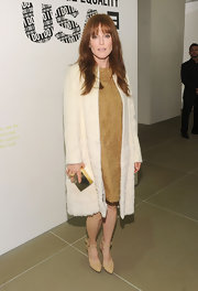 Julianne Moore donned a dusty cognac shift dress under a white textured coat for a retro style.