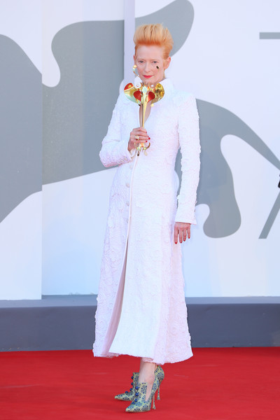 Tilda Swinton cut an elegant figure in a white guipure lace coat dress by Chanel Couture at the Venice Film Festival screening of 'The Human Voice.'