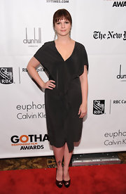 Amber dons a neutral toned cocktail dress with a simple cut and a soft center front ruffle.