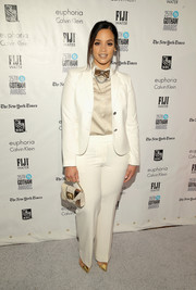 Dascha Polanco teamed her tuxedo with an elegant white and gold purse.