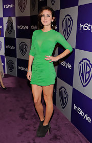 Jessica wore suede sky-high ankle boots with a vibrant green mini dress.