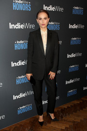 Natalie Portman complemented her suit with a black clutch by Tyler Ellis.