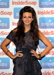 Michelle Keegan wore her hair pulled partly up for the Inside Soap Awards 2011. The look involves backcombing the front section then smoothing it and creating a very loose French braid along the top of her head. Before reaching the back of the head, the braid was secured with bobby pins.