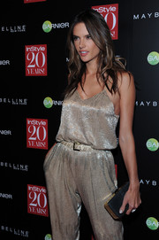 Alessandra Ambrosio teamed an elegant black and gold hard-case clutch with a sexy gold jumpsuit for the InStyle 20th anniversary party.