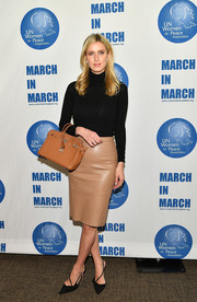 Nicky Hilton Rothschild paired her sweater with a tan leather pencil skirt by Lamarque.