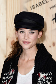Astrid Berges Frisbey attended the Isabel Marant photocall looking cool in a black captain's cap from the brand's collection with H&M.