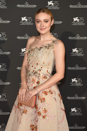 Dakota Fanning paired a beige Christian Louboutin clutch with a one-shoulder dress for the Jaeger-LeCoultre gala dinner at the Venice Film Festival.