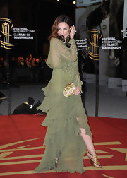 Elsa added a glam touch to her green chiffon gown with a gold satin clutch.