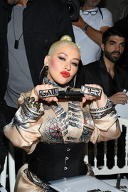 Christina Aguilera attended the Jean Paul Gaultier Couture show wearing a black corset belt with a printed kimono dress.