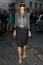 Carine Roitfeld softened her tough-chic outfit with a pair of nude satin ankle-tie sandals.